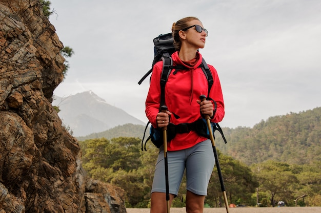 Girl in sunglasses standing on the rocks with hiking backpack and walking sticks