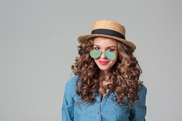 Ragazza in occhiali da sole e paglia