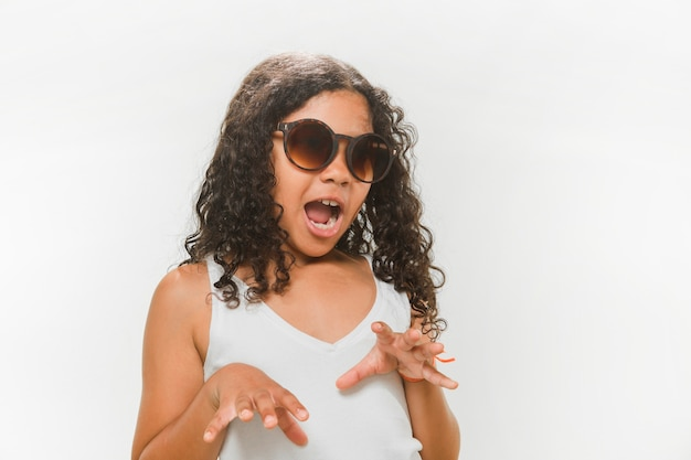 Girl in sunglasses trying to scare on white background