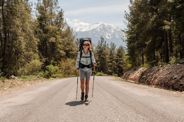 Girl in sunglasses walking on the road with hiking backpack and hiking sticks