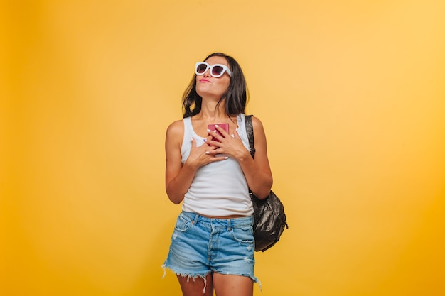 Girl in sunglasses on yellow background with backpack and passport