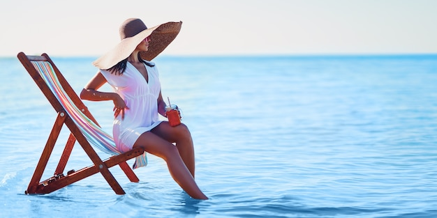Girl in sunhat and tunic sitting on the beach chair at seaside while holds cocktail summer vacation