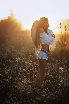 Girl at sunset in a hat. field of white flowers. dreadlocks. beautiful summer look