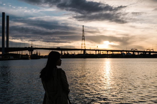 Girl sunset at sea and bridge