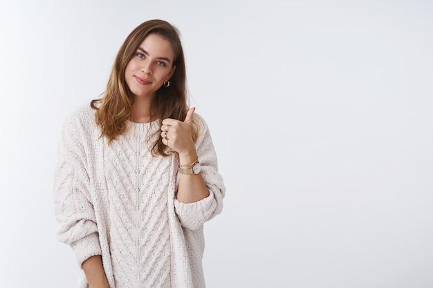 Девушка, поддерживающая вас, поднимает палец вверх, аплодирует, выражает точку зрения, любит продукт, одобряет, рекомендует услуги, наклоняет голову, довольная счастливо улыбается, выглядит нежно в уютном свободном свитере