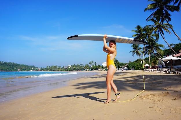 Girl surfer surfboard on her head