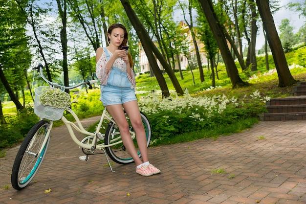 公園のバスケットに小さな白い花の花束を持って自転車に寄りかかってスマートフォンでインターネットサーフィンをしている女の子