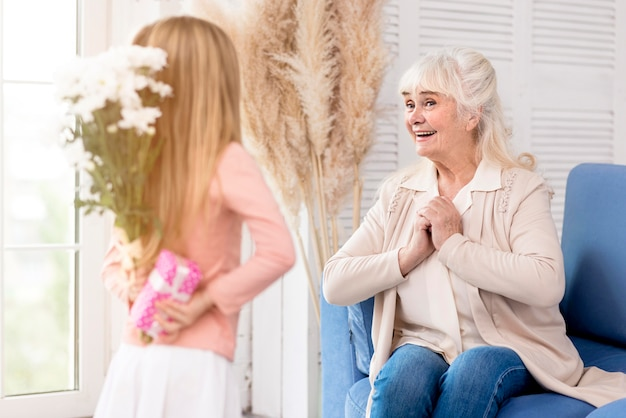 Girl surprising grandma on grandparents day