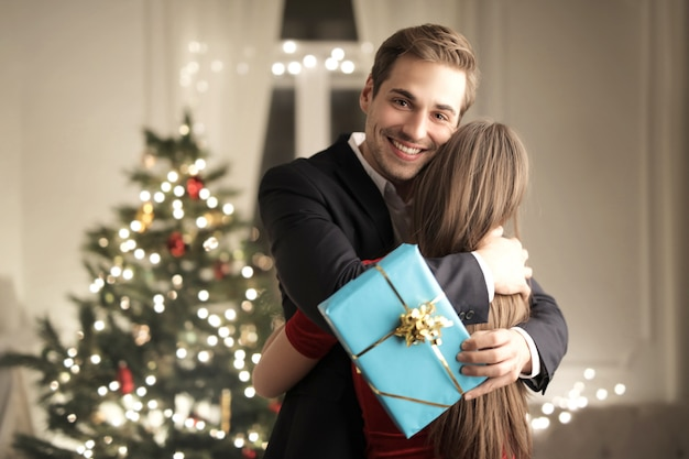 Girl surprising her boyfriend with a christmas gift
