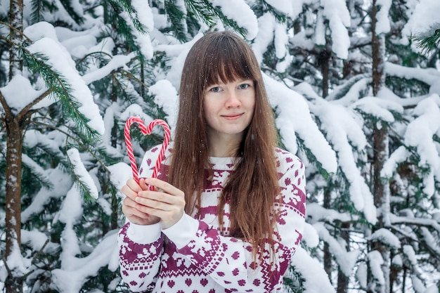 A girl in a sweater on the background of snow-covered trees