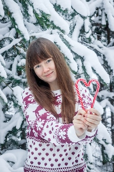 A girl in a sweater on the background of snow-covered trees .