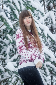 A girl in a sweater on the background of snow-covered trees.