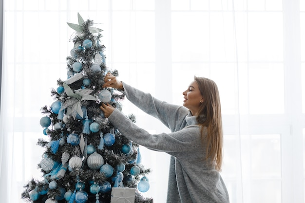 A girl in a sweater decorates a christmas tree, standing in front of the window. around the christmas tree are gifts. new year concept.