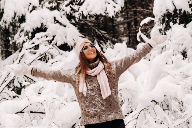A girl in a sweater and glasses in winter in a snow-covered forest.