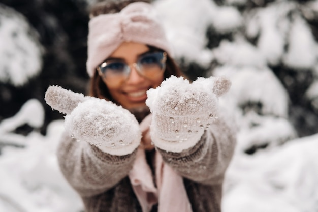 A girl in a sweater and glasses in winter in a snow-covered forest