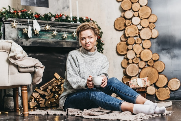 Girl in sweater holding a cup of coffee on background of a living room with a fireplace