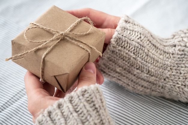 A girl in a sweater holds a gift decorated with her own hands. beautiful gift box made of kraft paper