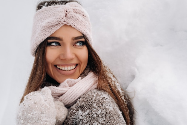 A girl in a sweater and mittens in winter stands on a snow-covered background.