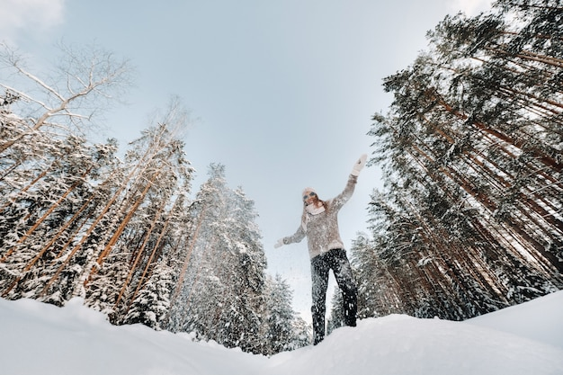A girl in a sweater and mittens in winter stands on a snow-covered background