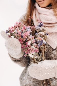A girl in a sweater in winter with a bouquet in her hands stands among large snowdrifts.