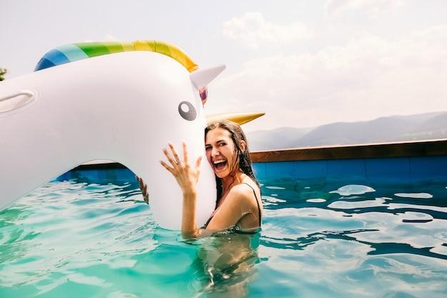 水泳と膨脹可能なユニコーンを保持している女の子