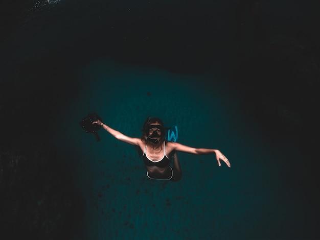 Девушка плывет глубоко в океане. красивое подводное фото.