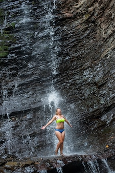 Girl in swimming suit standing under waterfall