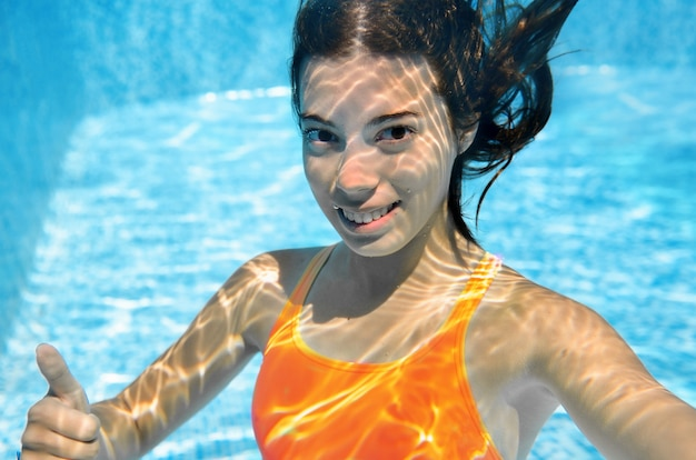 Girl swims in swimming pool underwater, happy active teenager dives and has fun under water