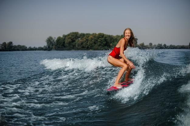 Girl in swimsuit on a board in sea