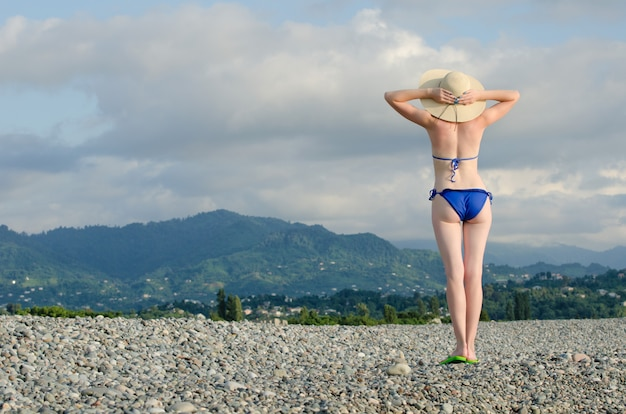 Girl in a swimsuit and hat looks at the mountains. back view
