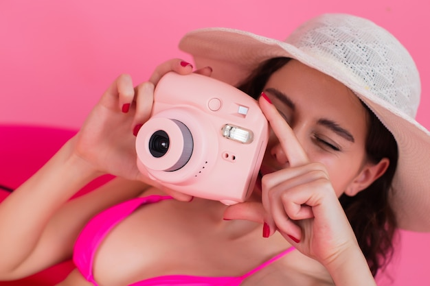 The girl in a swimsuit lies on an inflatable flamingo and takes a photo on the instant camera