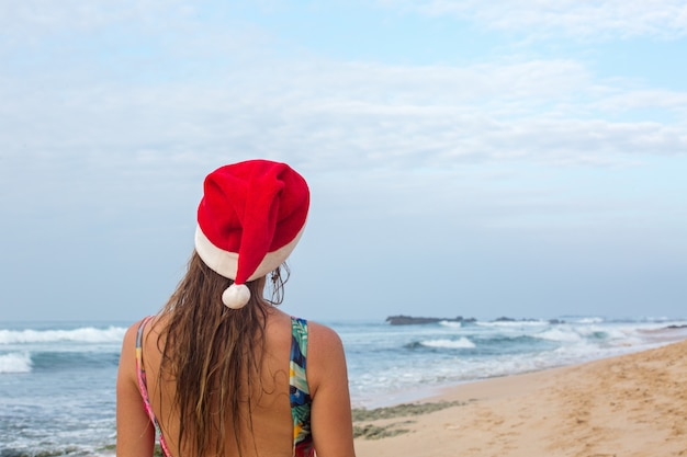 A girl in a swimsuit and santa's hat on the beach