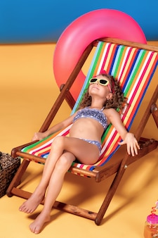 Girl in swimsuit and sunglasses lying in rainbow deck chair with crossed legs and sunbathing
