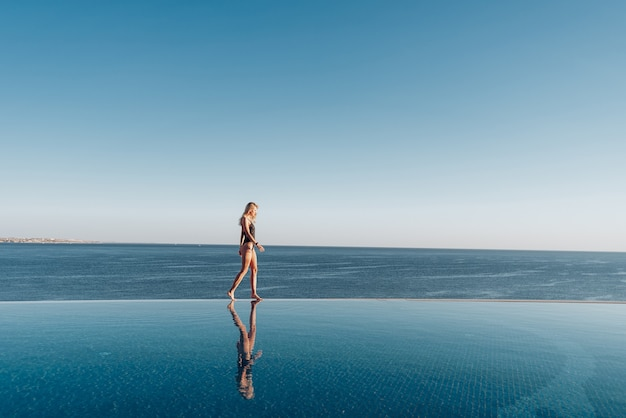 Girl in a swimsuit walks along the edge of the panoramic pool