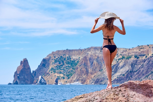 A girl in a swimsuit with curly hair holds a hat in the wind and looks out