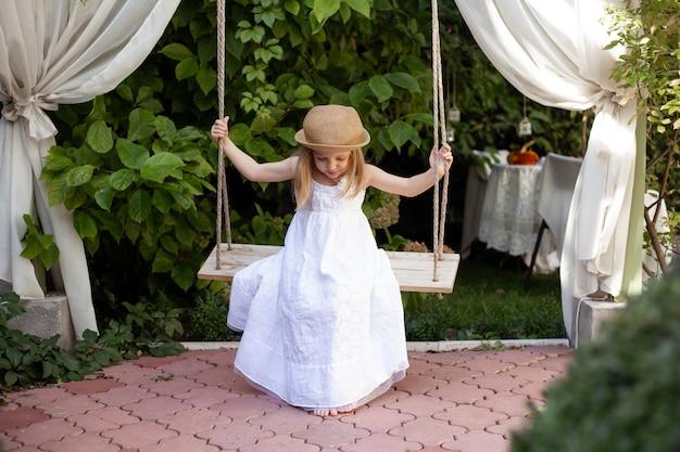 Девушка качается на качелях летом