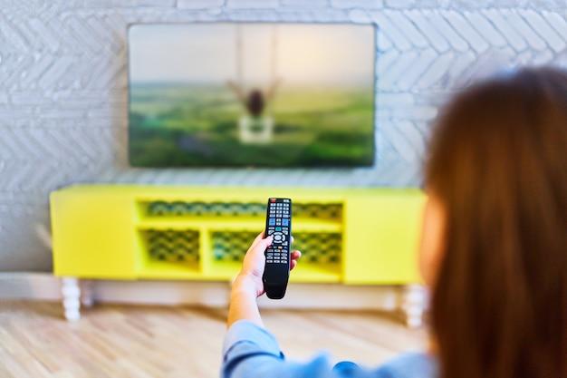 Девушка переключает каналы на пульте дистанционного управления и смотрит телевизор дома одна