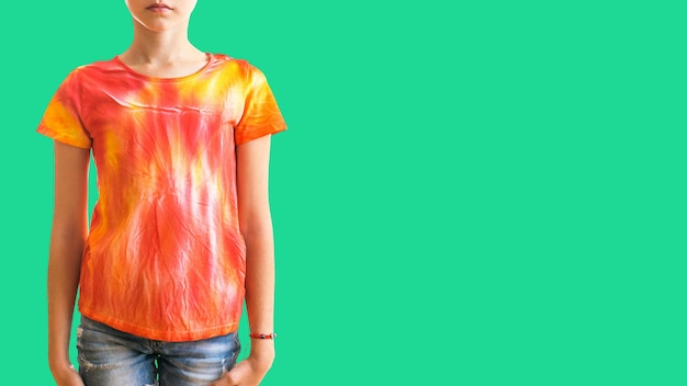 Girl in a t-shirt in the style of tie dye on a green surface