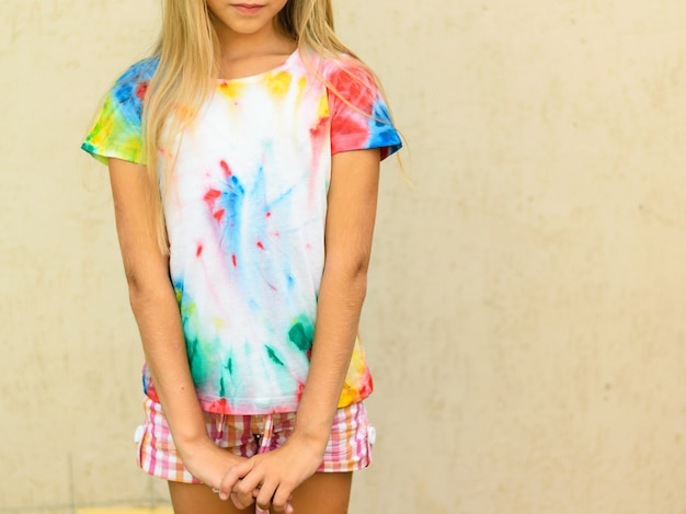 Girl in a t-shirt in the style of tie dye at the yellow wall.