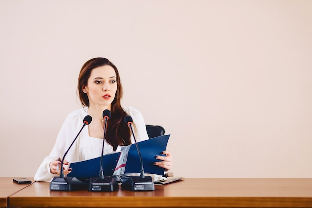 Girl at the table speaks in microphones at conference hall