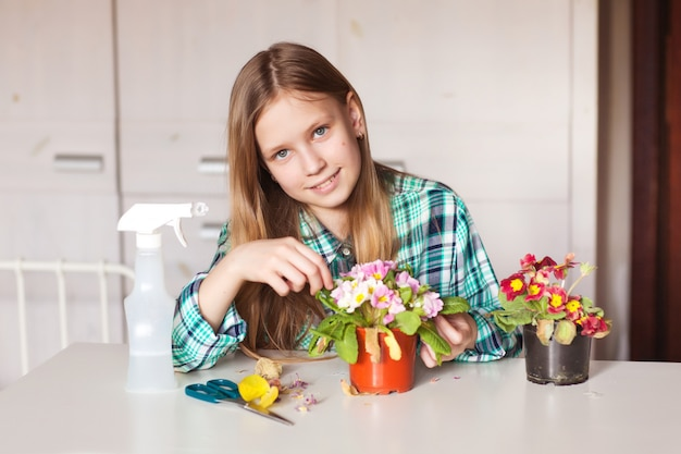 Girl take care of plants in her home