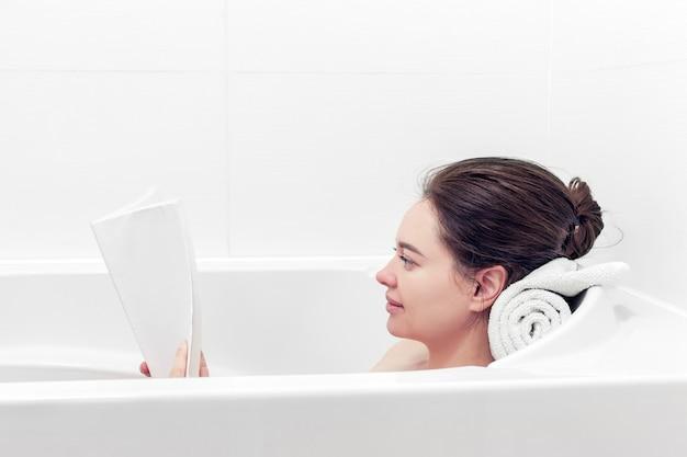 Девушка принимает ванну, читая книгу в белой ванной комнате