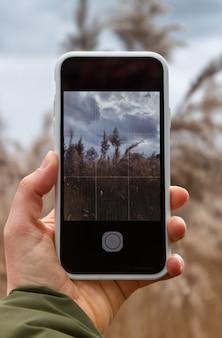 女の子は曇りの天気でパンパスグラスとフィールドの電話で写真を撮ります。