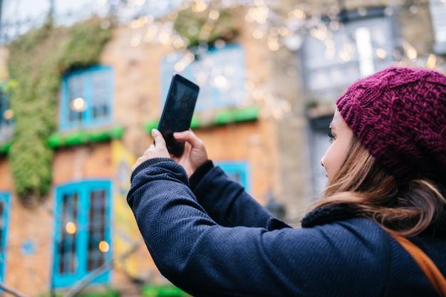 女の子は美しい町の通りで携帯電話で写真を撮る