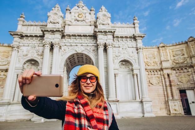 Девушка принимает selfie в квадрате перед dolmabahce, стамбулом, турцией. молодая девушка турист в шляпе и пальто фотографируется по телефону перед дворцом султана в стамбуле.