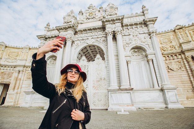소녀는 이스탄불, 터키 돌마 바흐 체 앞 광장에서 selfie를 걸립니다. 모자와 외 투에있는 어린 소녀 관광 이스탄불에서 술탄의 궁전 앞에서 전화에 촬영.