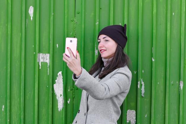 Девушка принимает селфи на зеленый гараж. носить шляпу и пальто. место для написания. одетый в холодную пагоду. одежда и стиль. природные эмоции