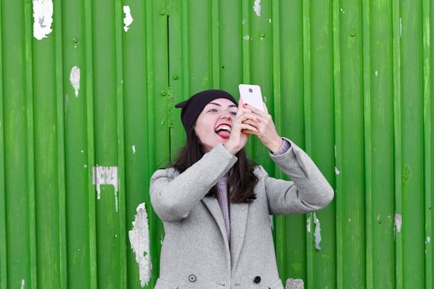 Девушка принимает selfie на зеленой промышленной двери. носить шляпу и пальто. место для написания. одетый в холодную пагоду. одежда и стиль. природные эмоции
