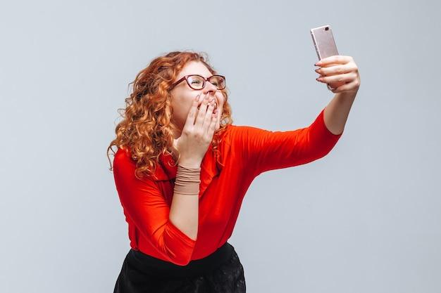 女の子は明るい灰色の背景で携帯電話で自分撮りを取ります