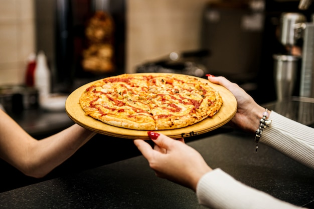 Девушка берет кусок пиццы. фастфуд, а не здоровый перекус. доставка еды на дом. красный перец, бекон, помидор, соус барбекю. закройте вверх.